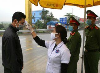 Nhân viên y tế đo thân nhiệt tại chốt số 3 sáng 2/4. Ảnh: Tất Định.