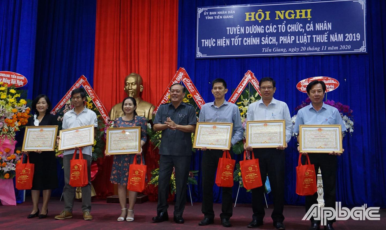 Đồng chí Lê Văn Nghĩa tặng Bằng khen của Chủ tịch Ủy ban nhân dân tỉnh cho 6 tập thể đã thực hiện tốt chính sách, pháp luật thuế năm 2019.