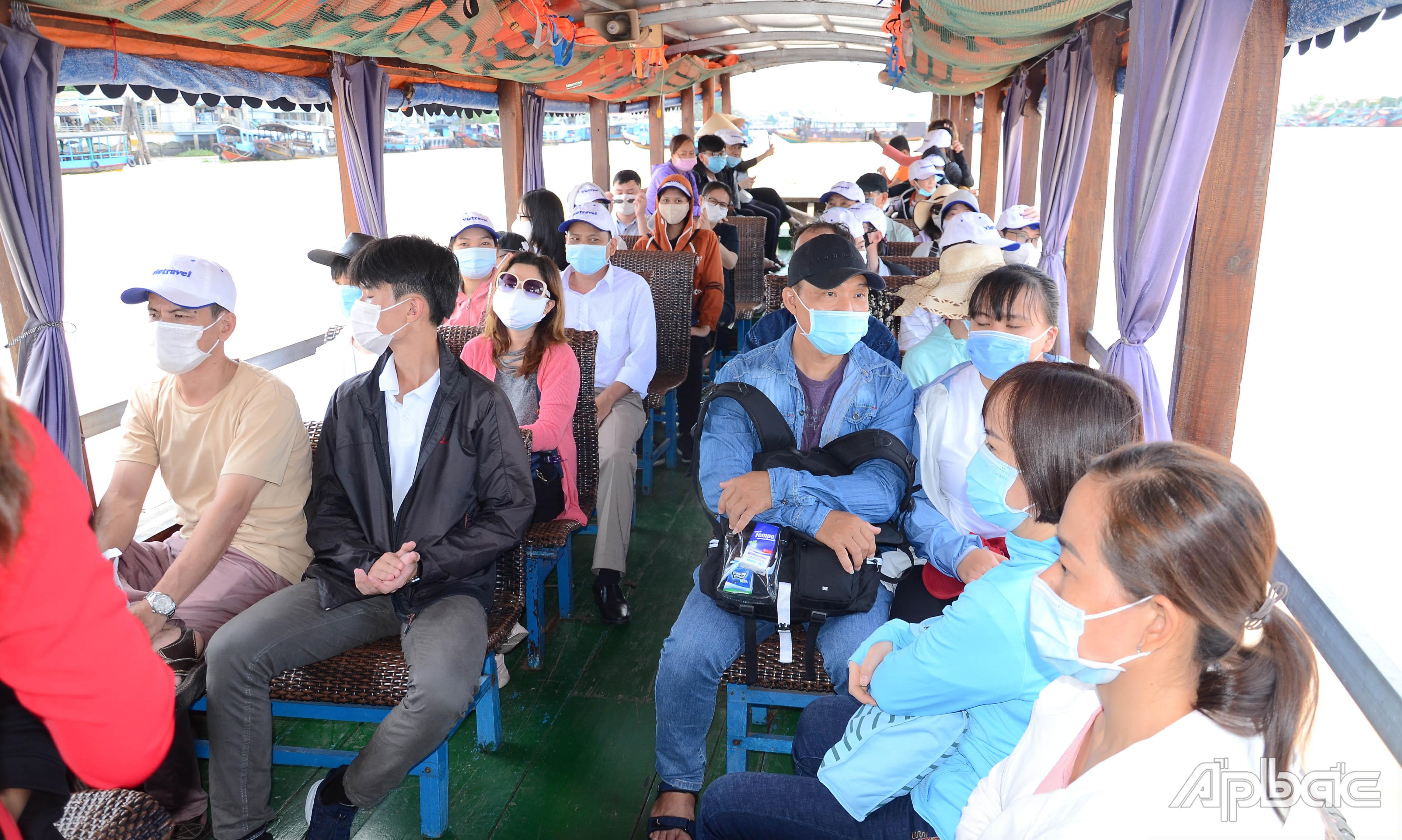 Khách du lịch xuống tàu di chuyển đến cù lao Thới Sơn.