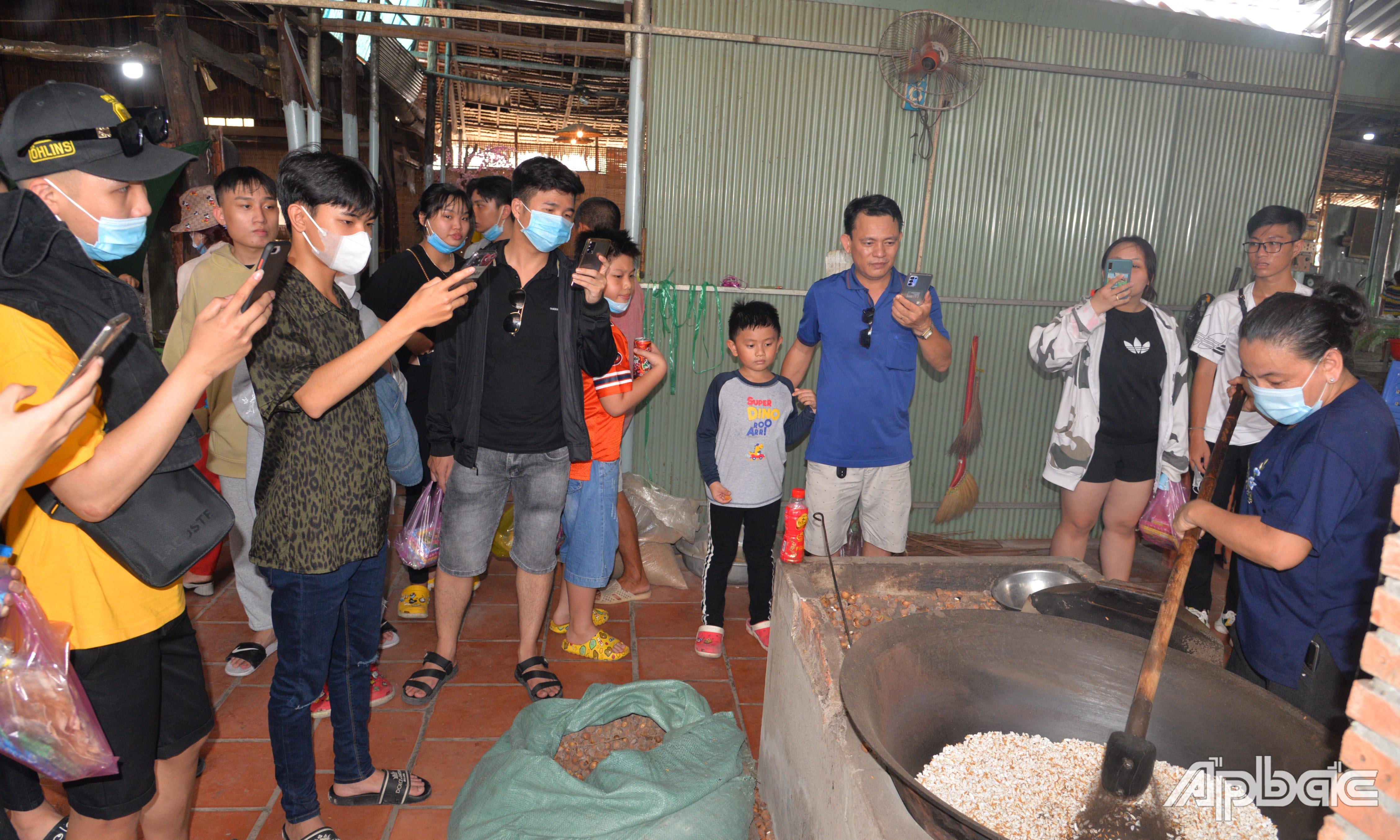 Khách tham quan trải nghiệm quy trình làm cốm ở Làng nghề  cốm An Ninh.