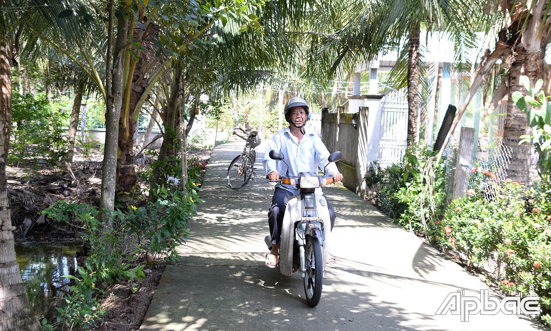 Ông Nguyễn Văn Mưa chạy xe gắn máy trên đường đan mà ông từng hiến đất.